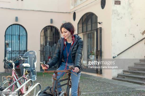 woman uses the phone with her bicycle - centro storico foto e immagini stock