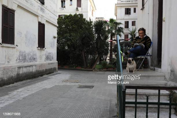 A woman uses the small space in front of her apartment to read a book on March 22 2020 in Rome Italy As Italy extends its nationwide lockdown to...