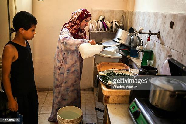 Woman uses water that her son brought with a bucket in Gaza City, Gaza on September 9, 2015. At least 120,000 Palestinians face water crisis just...