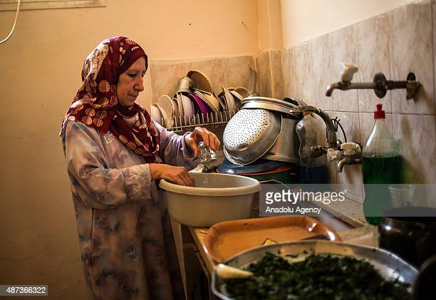 Woman uses water that her son brought with a bucket to wash the dishes in Gaza City, Gaza on September 9, 2015. At least 120,000 Palestinians face...