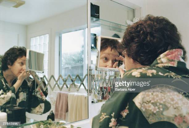 A woman using a bathroom mirror to put in her contact lenses January 1990