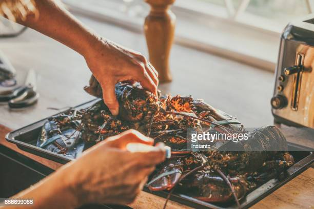 Woman, using a brush, is basting live Canadian lobsters with olive oil before she will grill them on the barbecue.