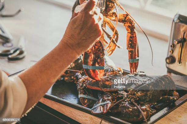 woman, using a brush, is basting live canadian lobsters with olive oil before she will grill them on the barbecue. - basting brush stock photos and pictures
