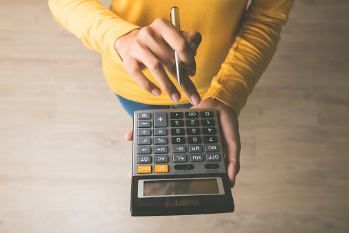Woman using a calculator with a pen in her hand 913332084