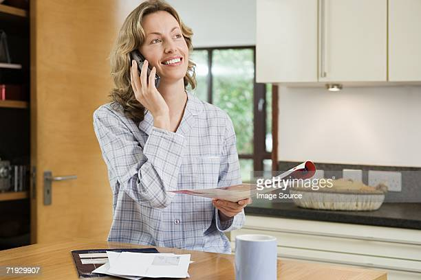 Woman using a cellular telephone in kitchen