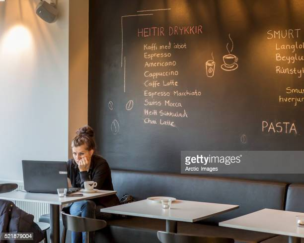 Woman using a computer in a cafe, Reykjavik, Iceland