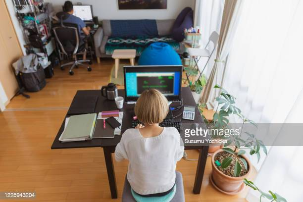 a woman using a computer in the living room of her home - makeshift stock pictures, royalty-free photos & images
