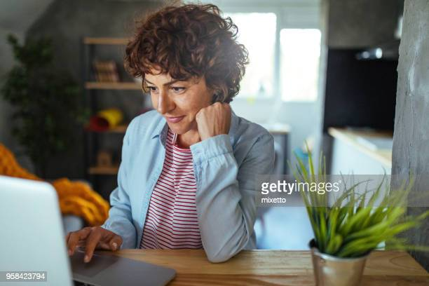 woman using a computer - mature women stock pictures, royalty-free photos & images