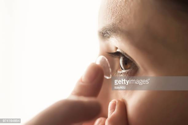 woman using a contact lens - contacts stock photos and pictures