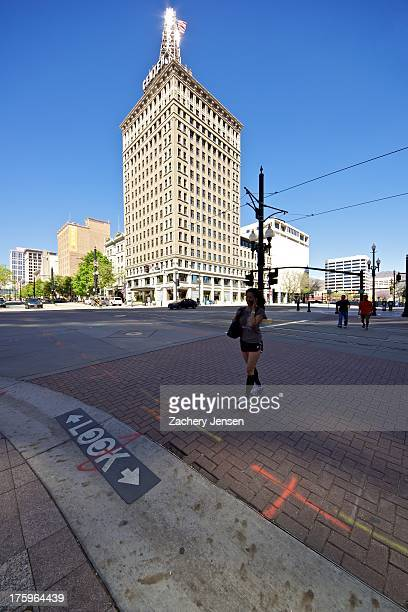 Woman using a crosswalk while talking on a cell phone in view of the Walker building in downtown Salt Lake City, Utah