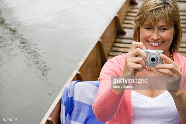 Woman using a digital camera on boat