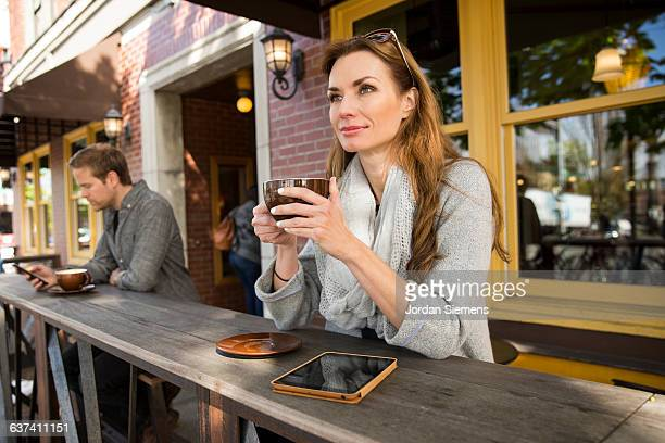 A woman using a digital tablet at a coffee shop.