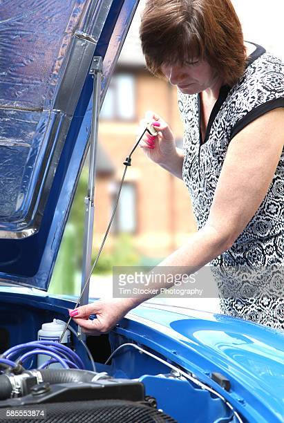 A woman using a dipstick to check the car engine oil level