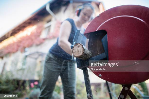Woman using a electric saw cutting fire wood.