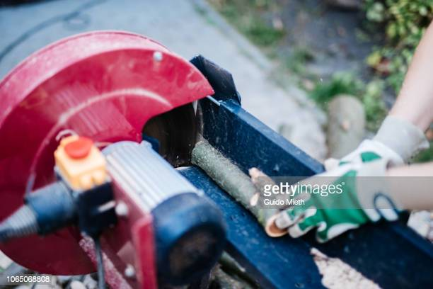 Woman using a electric saw.