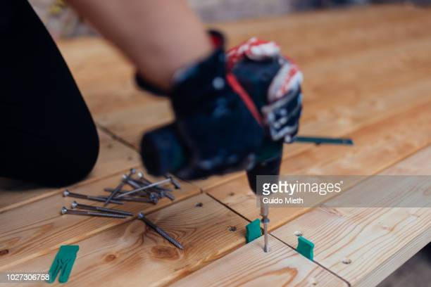 woman using a electric screwdriver. - screwdriver stock pictures, royalty-free photos & images