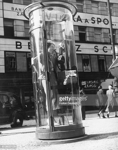 A woman using a futuristic soundproof telephone booth in 1938