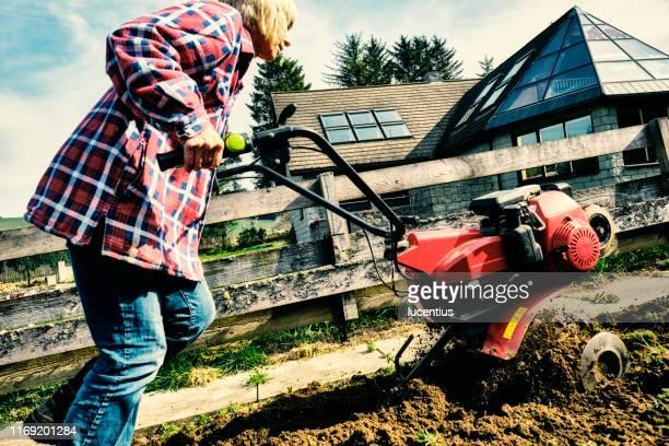 woman using a garden rotovator - tiller stock photos and pictures