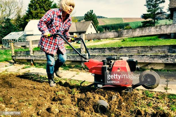 woman using a garden rotovator - one senior woman only stock pictures, royalty-free photos & images