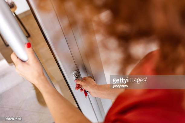 woman using a house key on the front door. - unlocking stock pictures, royalty-free photos & images