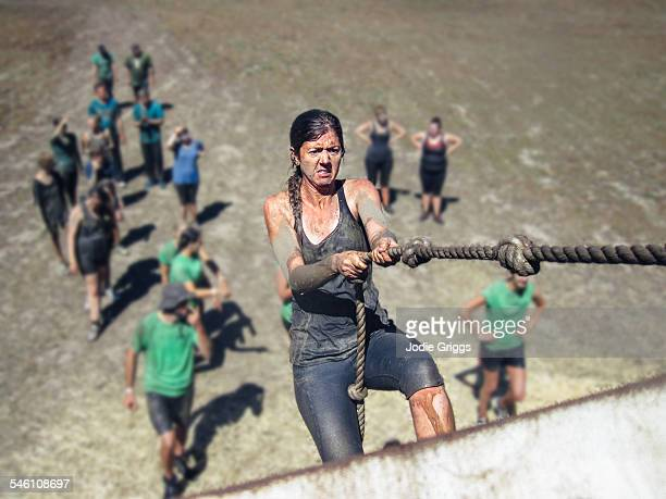 woman using a knotted rope to climb a large wall - obstacle course stock photos and pictures