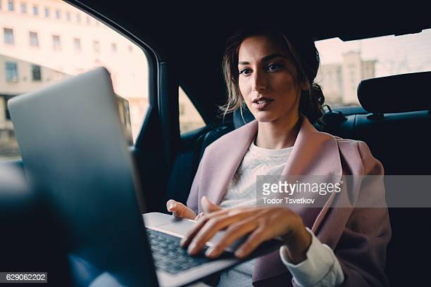 Woman using a laptop in a car