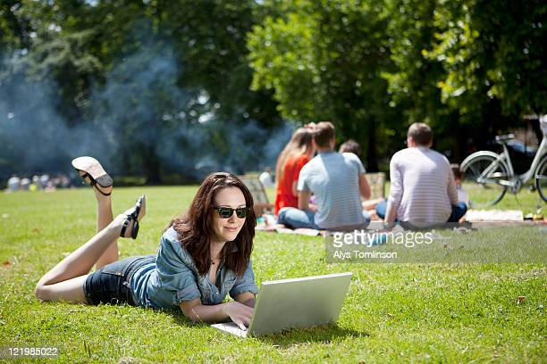 a woman using a laptop in a city park - park city stock photos and pictures