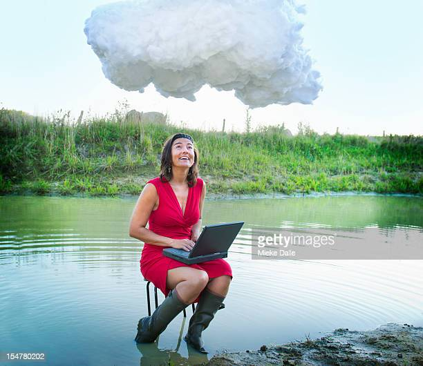 A woman using a laptop in a pond under a cloud