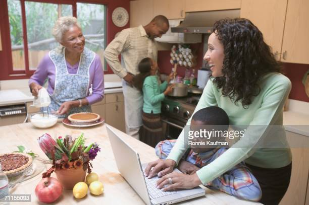 Woman using a laptop in busy kitchen