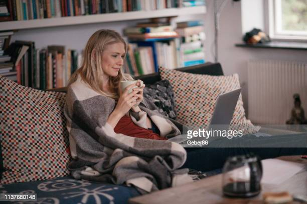 woman using a laptop - cosy stock pictures, royalty-free photos & images