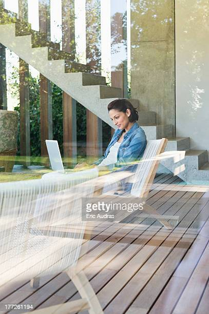 Woman using a laptop viewed through from a glass wall