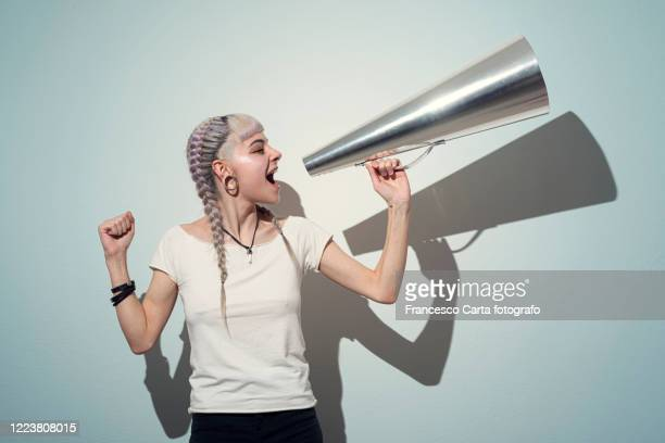woman using a megaphone - protestor stock pictures, royalty-free photos & images