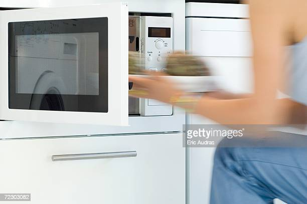 Woman using a microwave, close-up