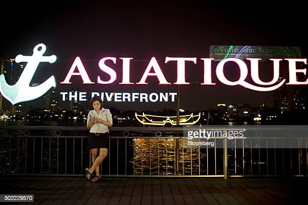 A woman using a mobile device stands on the waterfront below an illuminated sign for Asiatique The Riverfront openair mall at the night market in...