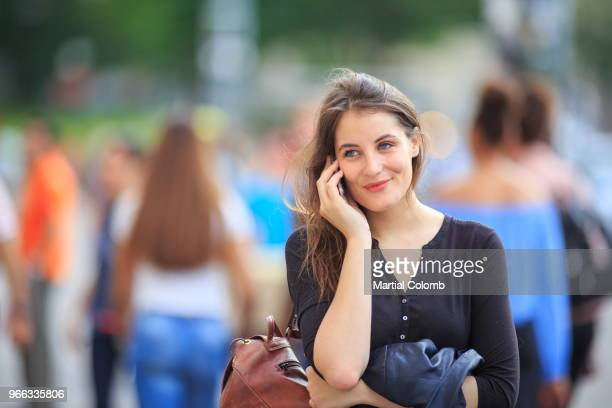 woman using a phone among a crowd in PARIS