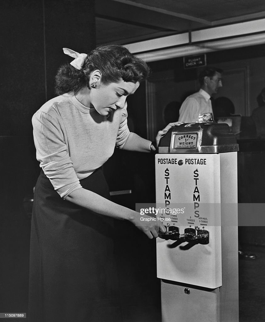 A Woman Using A Postage Stamp Vending Machine At The Post