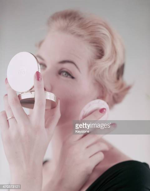 A woman using a powder compact 1954