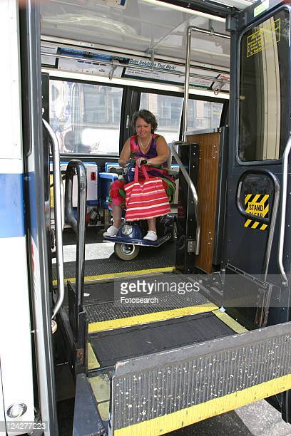 Woman using a scooter/cart for mobility getting off a city bus via a lift.