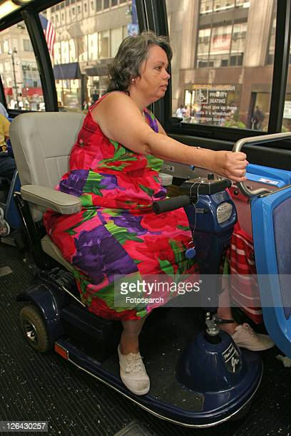 Woman using a scooter/cart for mobility riding a city bus.