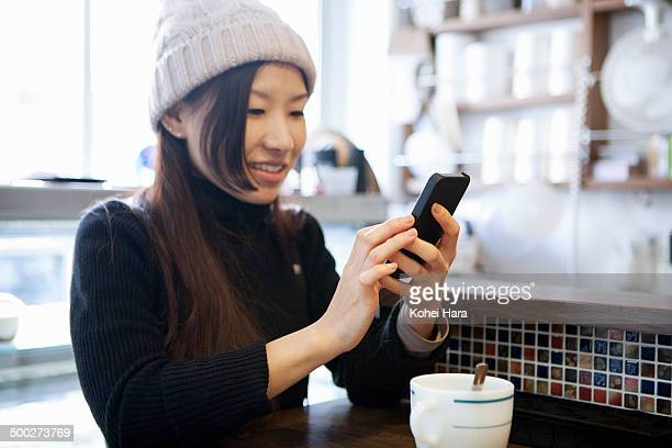 woman using a smart phone at cafe