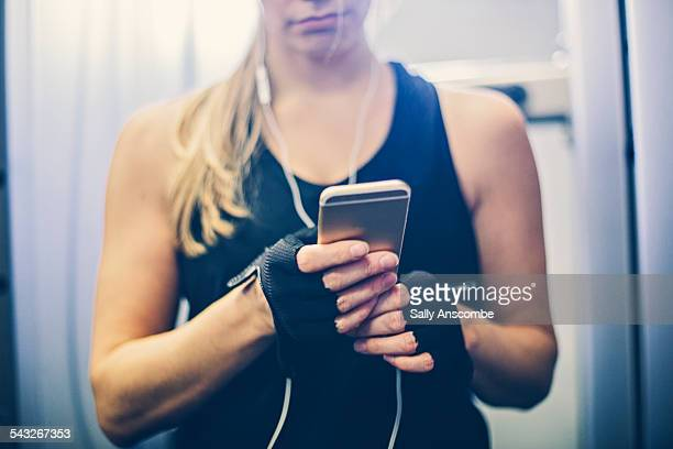 woman using a smart phone at the gym - vest stock photos and pictures