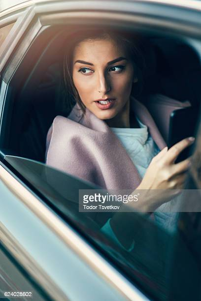 Woman using a smart phone in a car