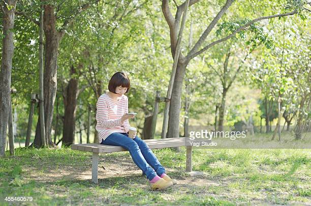 woman using a smart phone in the green - ベンチ ストックフォトと画像
