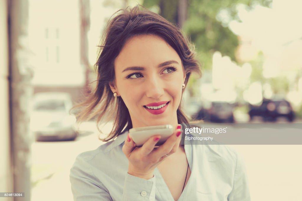Frau mit einem Smartphone Spracherkennung funktionieren Online-zu Fuß auf einer Stadtstraße : Stock-Foto