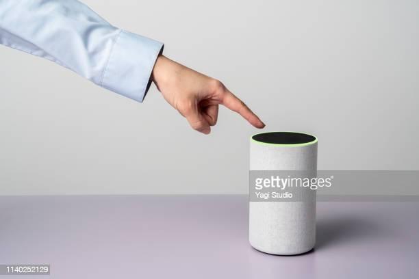 woman using a smart speaker with smart phone. - voce foto e immagini stock