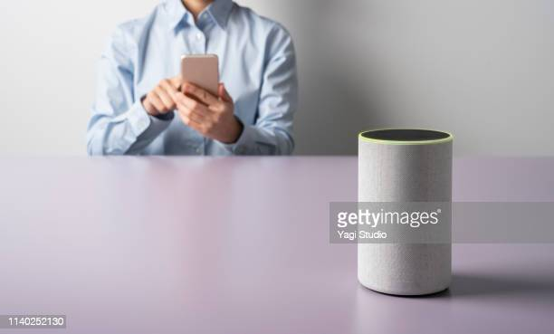 woman using a smart speaker with smart phone. - mid section stock pictures, royalty-free photos & images