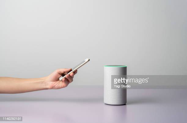 woman using a smart speaker with smart phone. - 可動性 ストックフォトと画像
