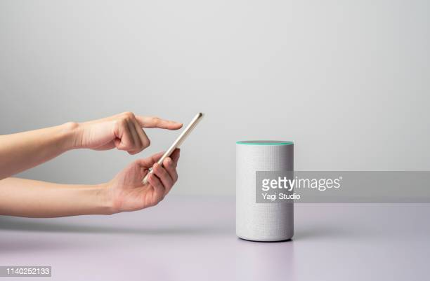 woman using a smart speaker with smart phone. - comunicação imagens e fotografias de stock