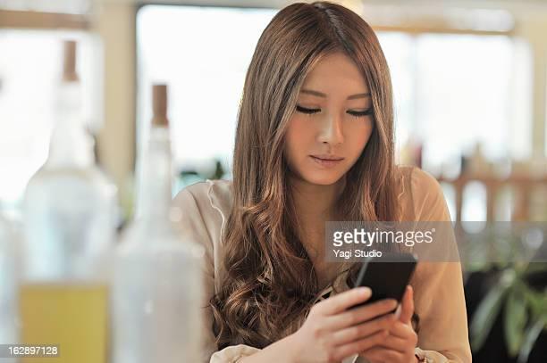 woman using a smartphone in a cafe - femme japonaise belle photos et images de collection