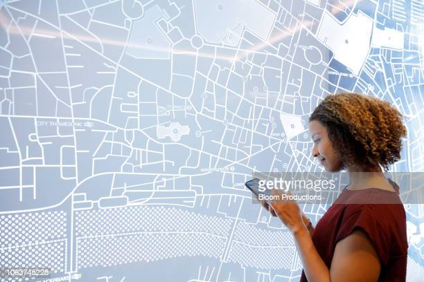 woman using a smartphone, next to a futuristic digitally generated display - karte navigationsinstrument stock-fotos und bilder